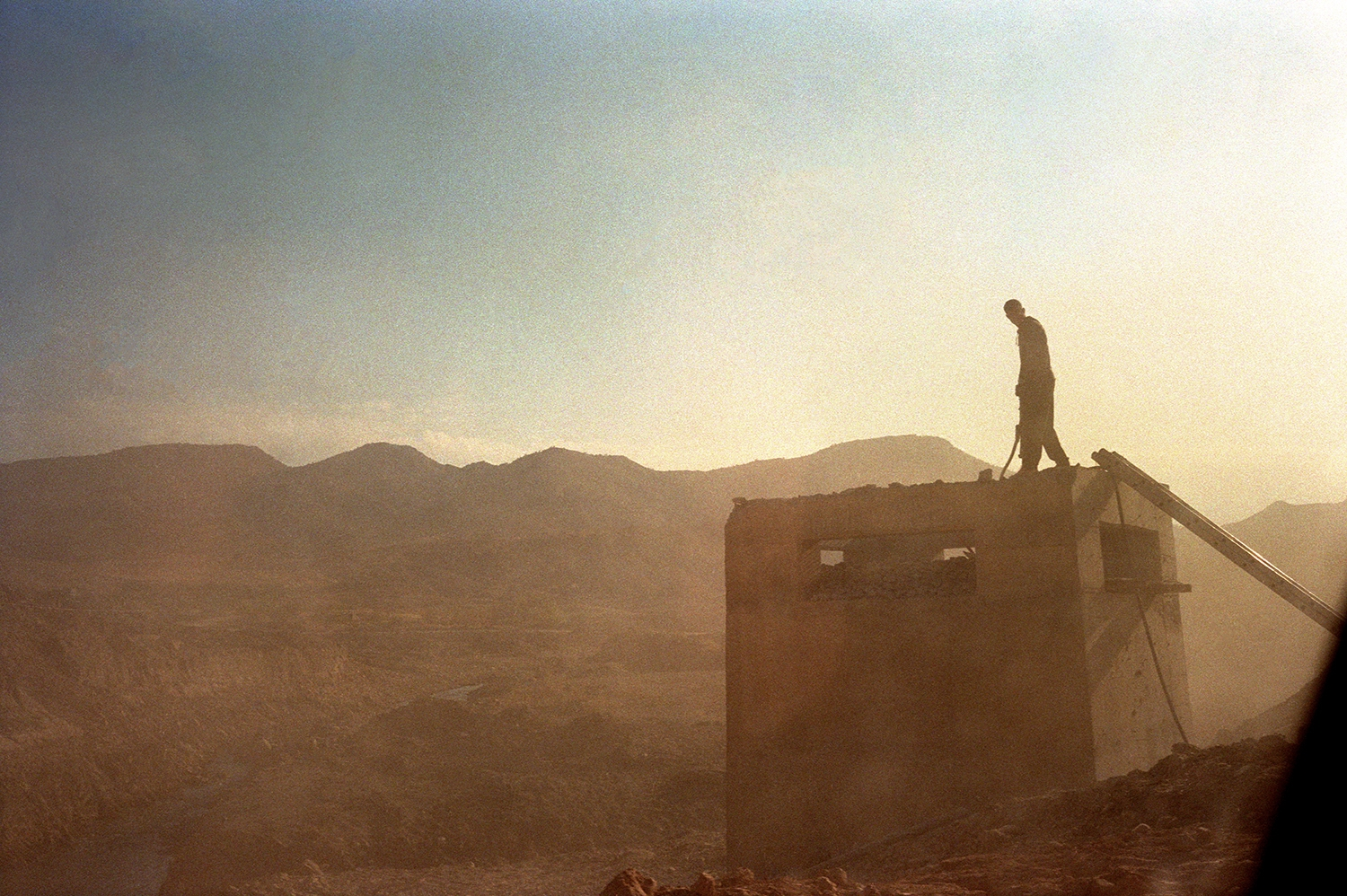 May 2014 - Koya mountains, Iraq - A man works on the roof of a building on the side of the street between Erbil and Sulaiymaniyah.